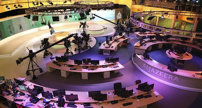 In this Jan. 1, 2015, file photo, staff members of Al-Jazeera International work at the news studio in Doha, Qatar. (AP Photo)