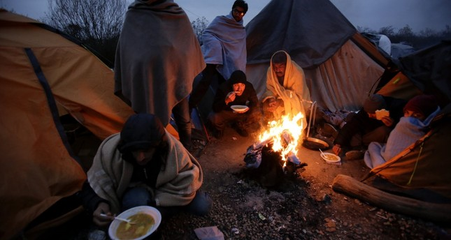 Migrants, seen below eating around a fire at a camp in Velika Kladusa, close to the Croatian border, remain stuck there as winter approaches.