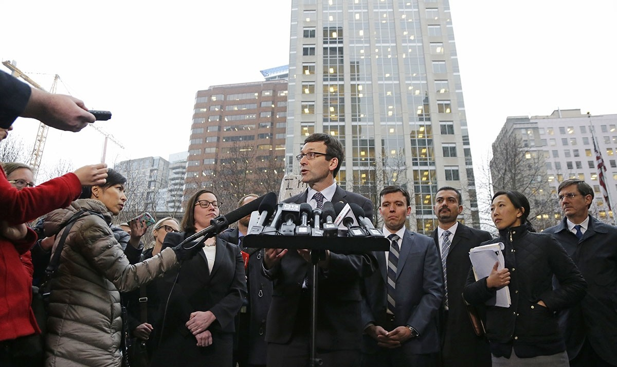 Washington Attorney General Bob Ferguson, center, talks to reporters Friday, Feb. 3, 2017, following a hearing in federal court in Seattle. (AP Photo)