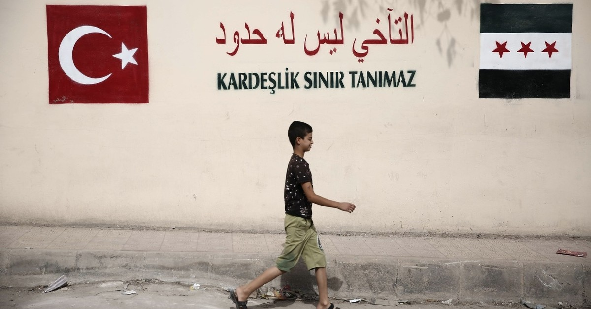 A Syrian boy walks past graffiti saying ,Brotherhood Beyond Borders,, in the northern Syrian town of Azaz on the border with Turkey, Oct. 16, 2018.