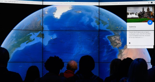 Google earth gets revamped with interactive guided tours 3d maps people look at a google earth map on a screen as google earth unveils the revamped gumiabroncs Choice Image