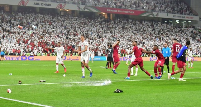 Fans throw bottles and flip-flops at the pitch during the 2019 AFC Asian Cup semifinal football match between Qatar and UAE at the Mohammed Bin Zayed Stadium in Abu Dhabi on Jan. 29, 2019.
