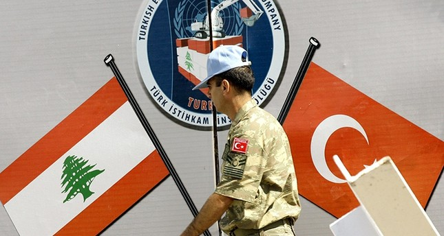 A member of the Turkish engineering contingent in the United Nations Interim Force in Lebanon (UNIFIL) walks past a wall depicting flags (AFP Photo)
