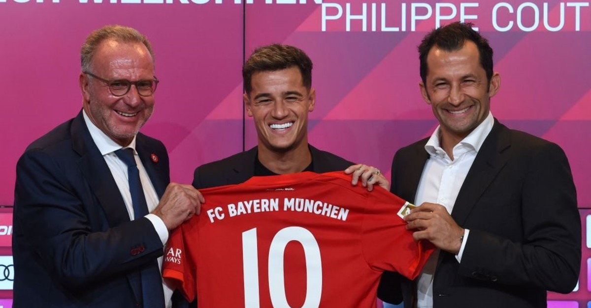 Bayern Munich CEO Karl-Heinz Rummenigge (L), sports director Hasan Salihamidzic (R) and Philippe Coutinho, pose with his jersey in the stadium in Munich, Aug. 19, 2019.