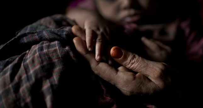 In this Monday, June 25, 2018, photo, S holds her baby boy's hand as she sits in her shelter in Balukhali refugee camp in Bangladesh. (AP Photo)