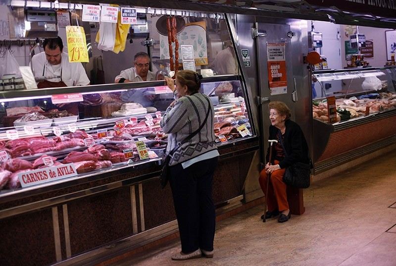 Customers buy meat at a butcher at Madrid's Chamberi market April 12, 2011. (Reuters Photo)