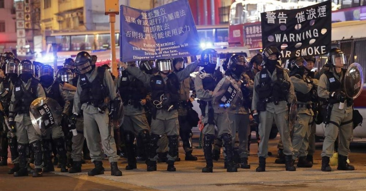 Riot police hold banners warning people not to take out any processions, Hong Kong, Dec. 25, 2019. (AP Photo)