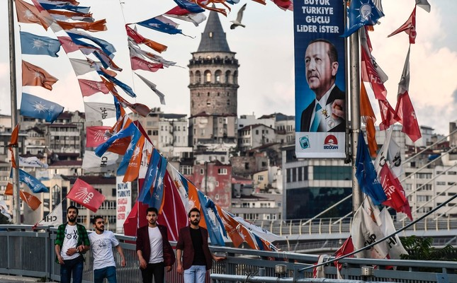 Onlookers pass by party campaign banners and a portrait of President Erdoğan for the upcoming elections, Istanbul, June 18.