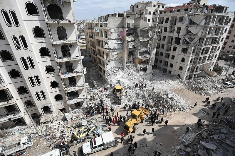Syrian rescue clear the rubble in the morning of April 10, 2018 at the site of an explosion of unknown origin which wrecked a multi-storey building the previous night in the war-battered country's northwestern city of Idlib. (AFP Photo)