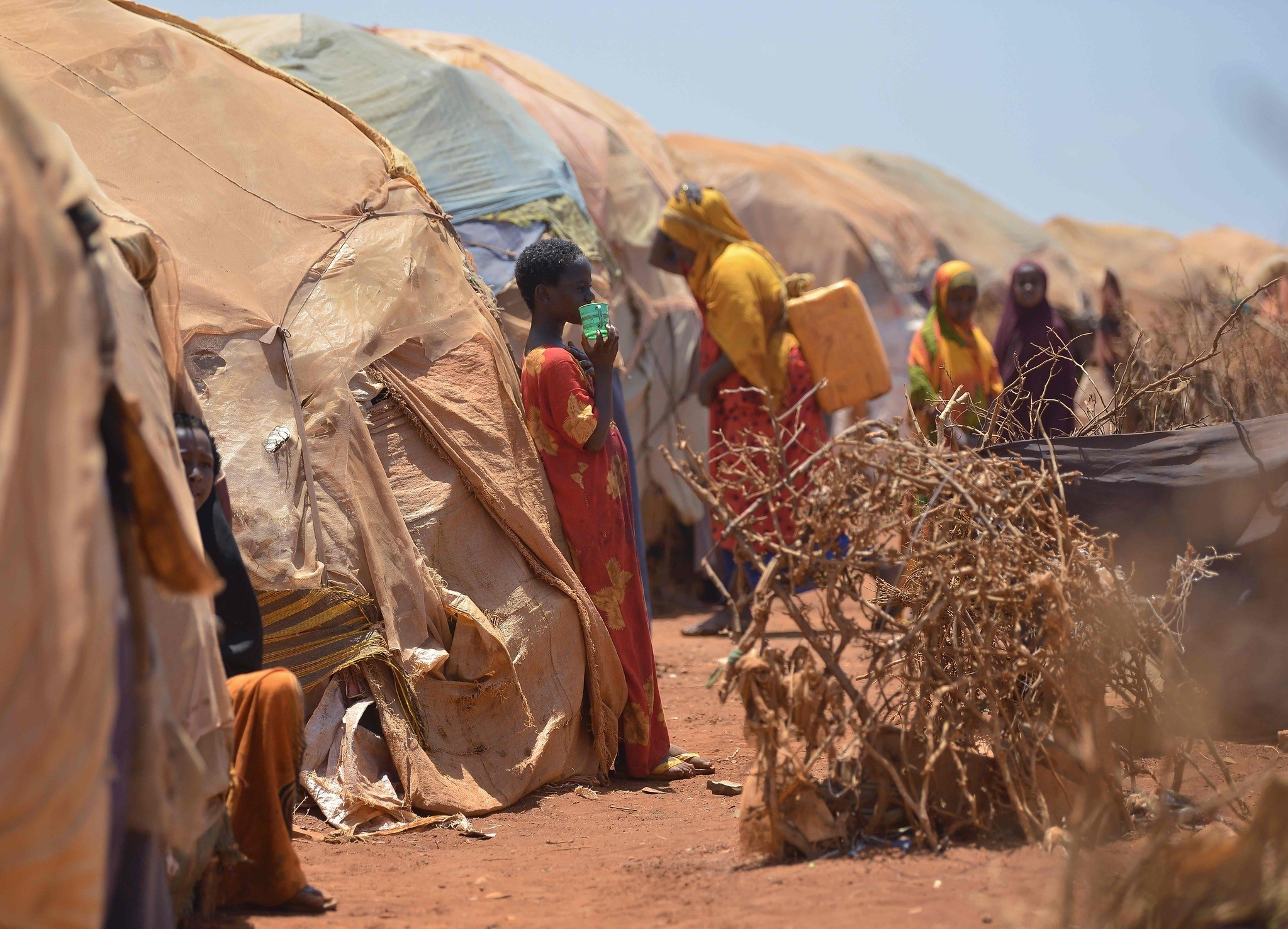 Internally displaced families stand next to their huts on March 14, 2017 at a makeshift camp on the outskirts of Baidoa. (AFP Photo)