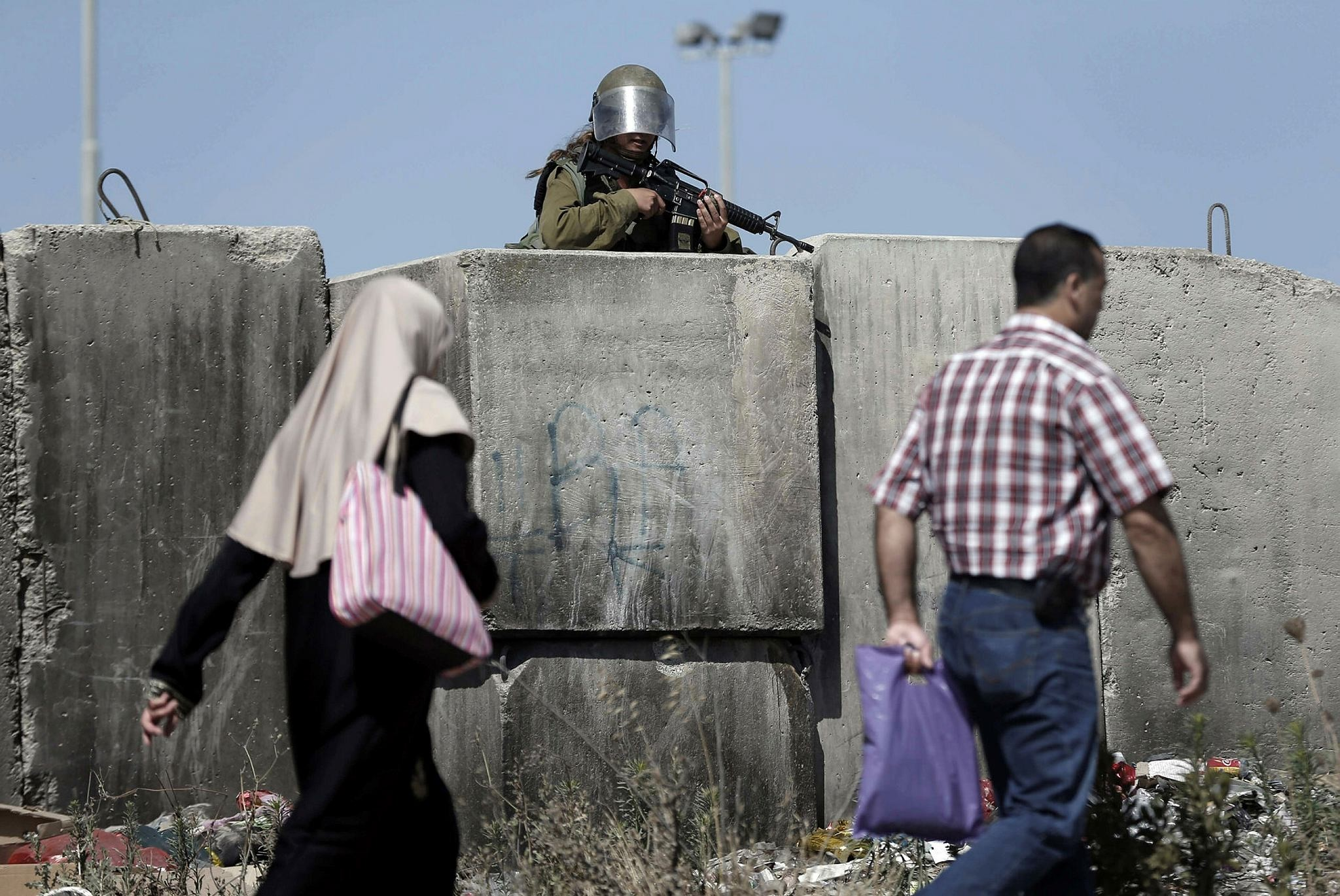 A female Israeli soldier stands guard at the Qalandia checkpoint, south of Ramallah, as thousands of Palestinians wait to cross from the West Bank to Jerusalem.