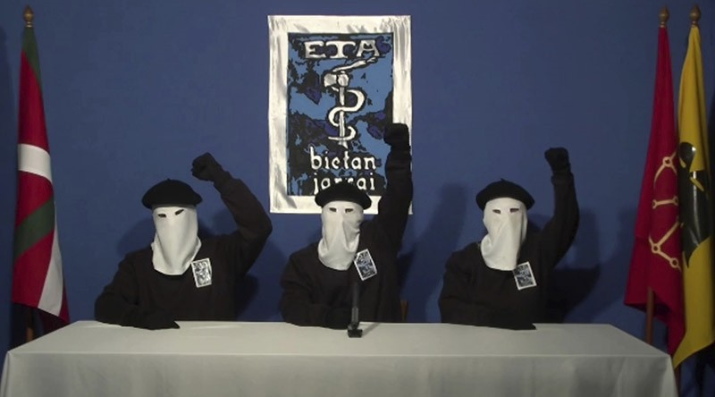 In this file image made from video provided on Oct. 20, 2011, masked members of the Basque separatist group ETA hold up their fists in unison following a news conference at an unknown location. (AP Photo)