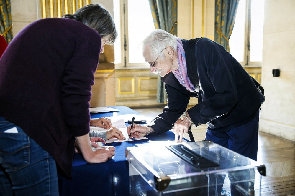 A man signs his name before casting his ballot for the French Senate elections at the Hotel de Ville of Paris on Sept. 24.