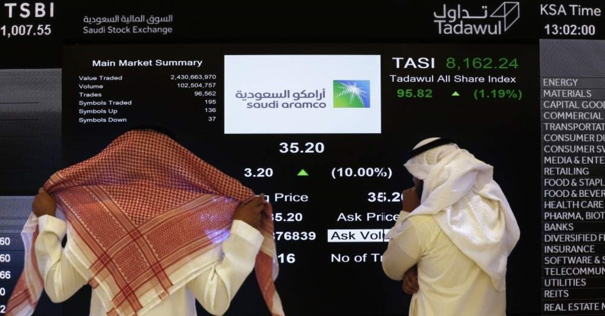 In this Dec. 11, 2019, file photo, the Saudi stock market officials watch the stock market screen displaying Saudi Arabia's state-owned oil company Aramco after the debut of Aramco's initial public offering (IPO) on the Riyadh's stock market in Riyadh, Saudi Arabia. (AP Photo)