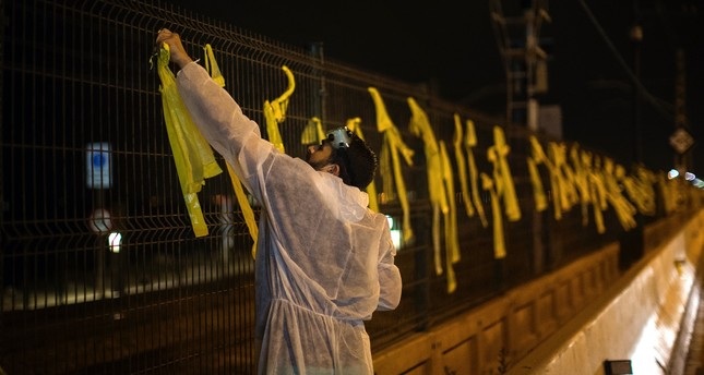 A man removes yellow  ribbons placed on a fence by Catalan separatists, Premia del Mar, Sept. 4.