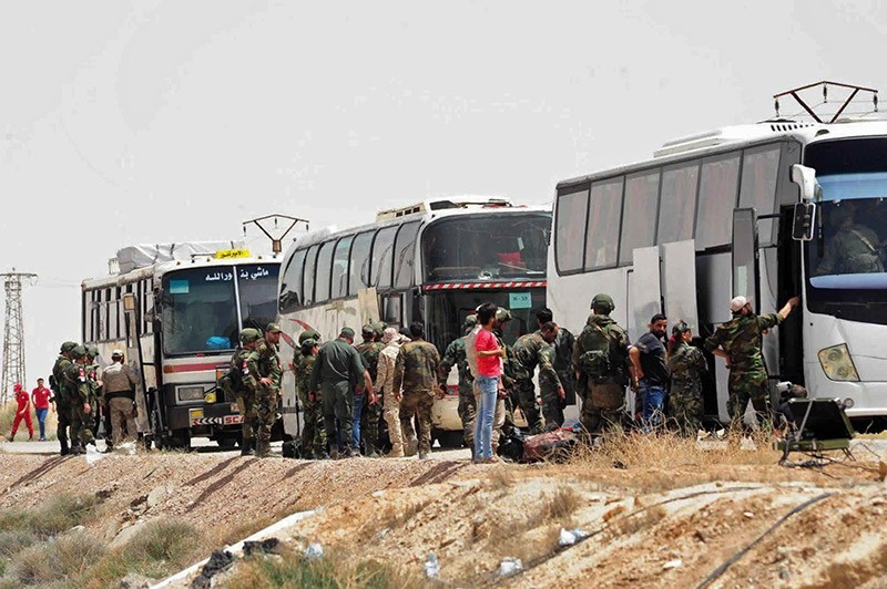 This photo released by the SANA news agency, shows Russian soldiers and regime forces overseeing the evacuation of opposition fighters and their families from the town of Dumayr, northeast of Damascus, Syria, April 19, 2018. (AP Photo)