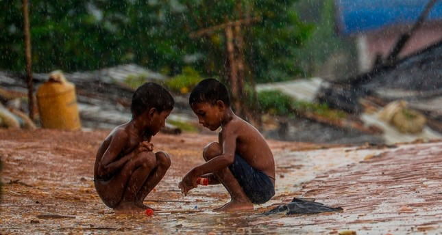 Rohingya refugee children play during a rainfall at the Kutupalong Rohingya refugee camp in Bangladesh's Ukhia district on  Aug. 24, 2019 AFP Photo