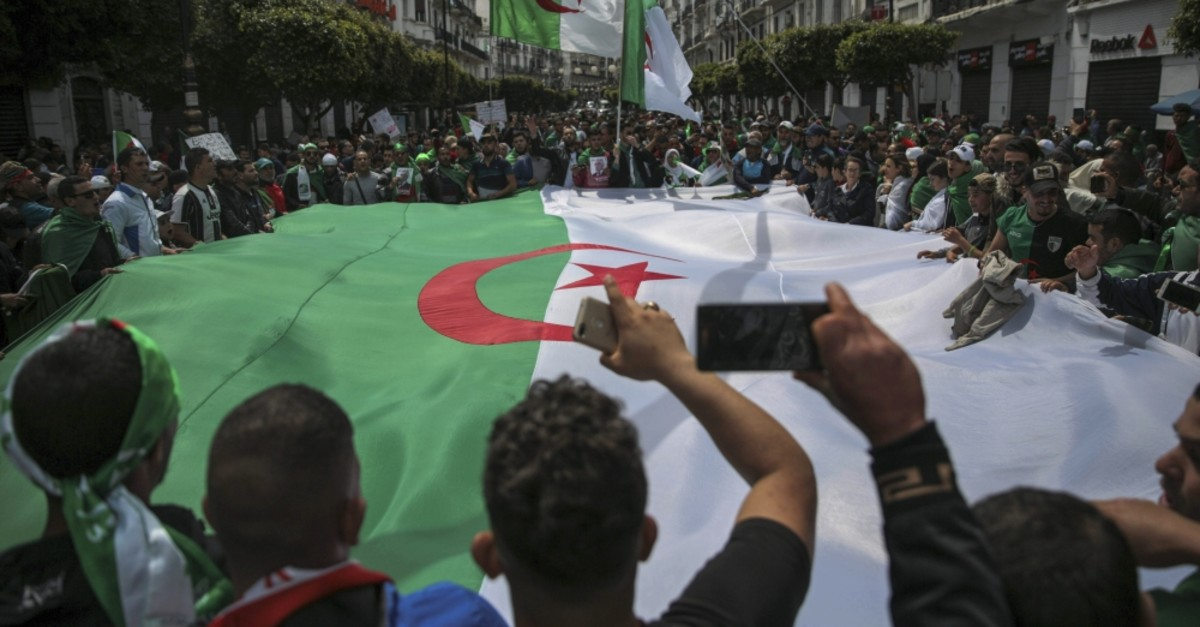 Protesters carry a large flag and chant slogans during a demonstration against the country's leadership, in Algiers, April 12, 2019.