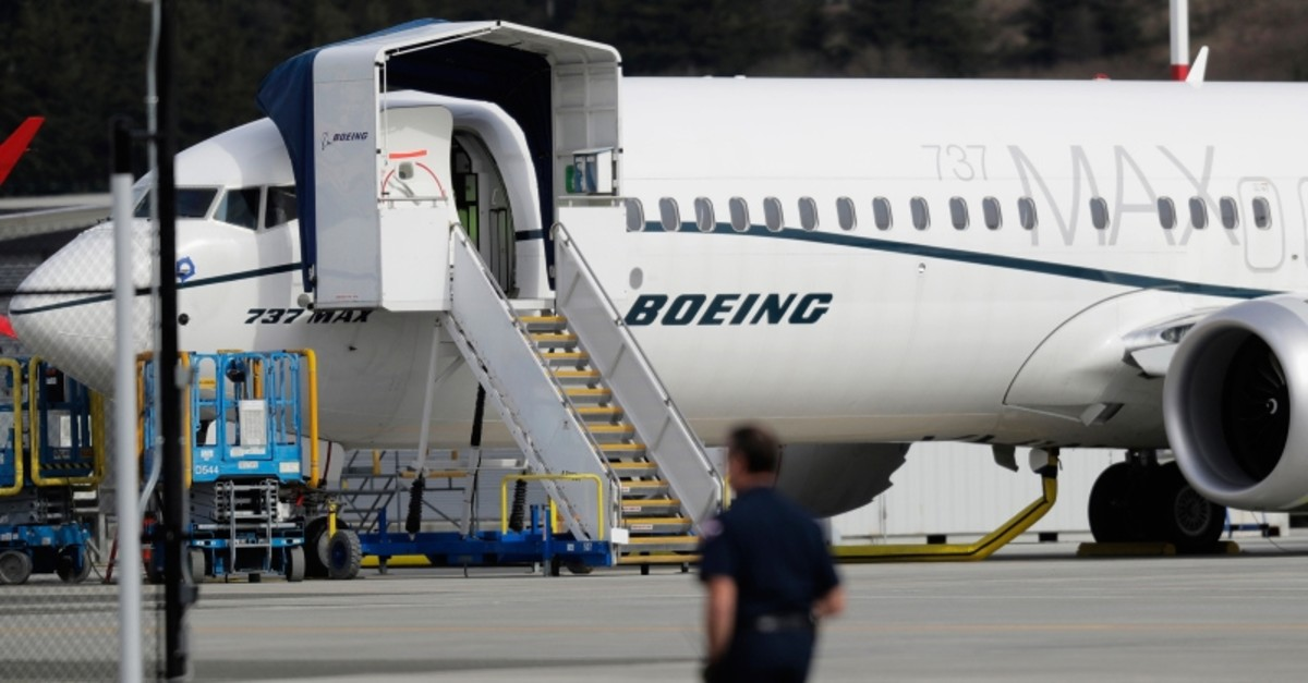 In this March 14, 2019, file photo, a worker walks next to a Boeing 737 Max 8 airplane parked at Boeing Field in Seattle. (AP Photo)