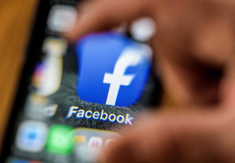 An illustration picture taken through a magnifying glass on March 28, 2018 in Moscow shows the icon for the social networking app Facebook on a smart phone screen. (AFP Photo)