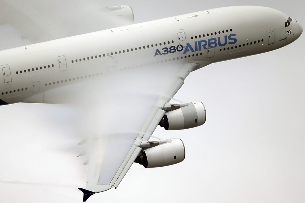 Vapor forms over the wings of an Airbus A380 as it performs a demonstration flight at Paris Air Show. Airbus says it will stop making its costly A380 superjumbo if it cannot strike a long-term deal with Emirates for a steady supply of the planes.