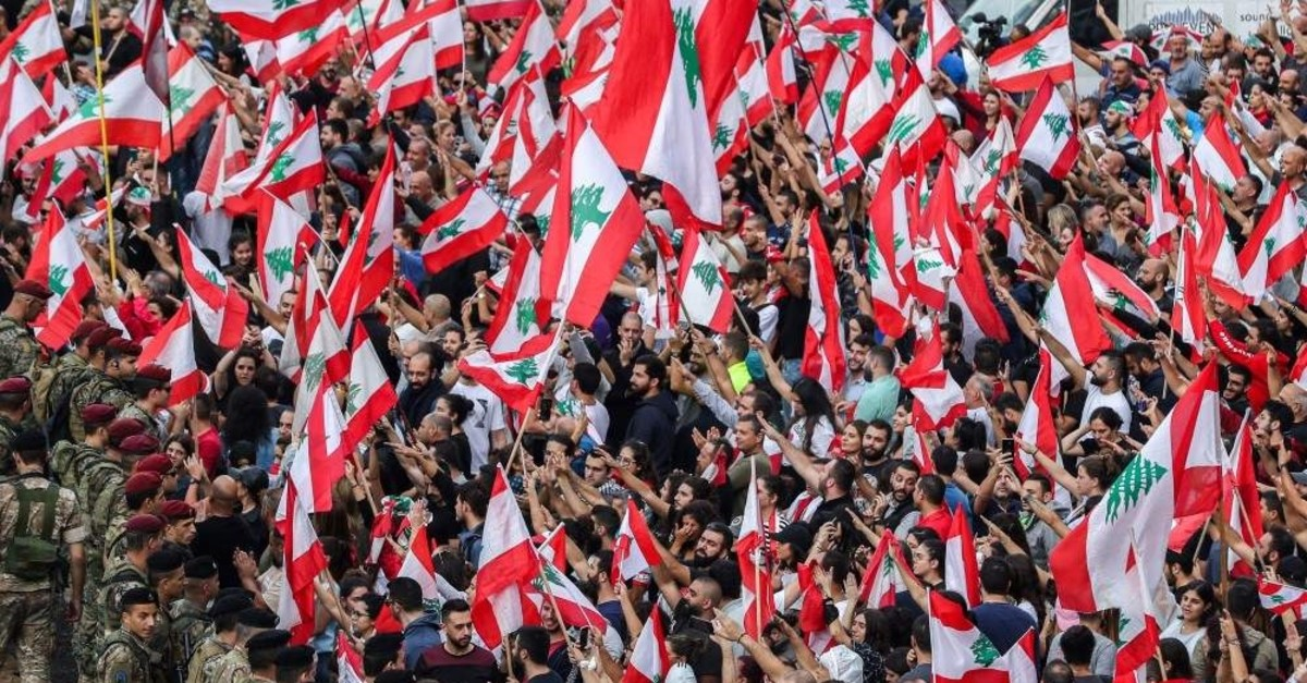Protesters wave the Lebanese national flag in front of soldiers, Beirut, Oct. 23, 2019. (AFP Photo)