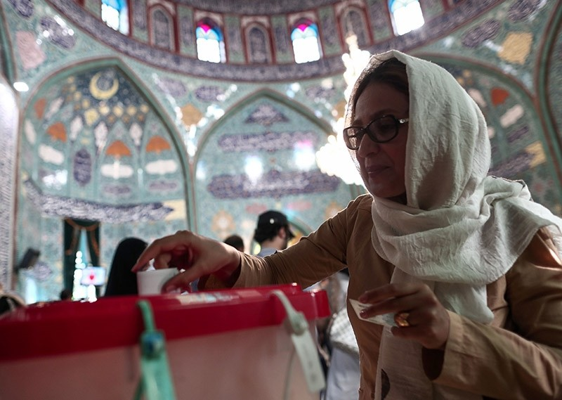 An Iranian woman casts her ballot for the presidential elections at a polling station in Tehran on May 19, 2017 (AFP Photo)