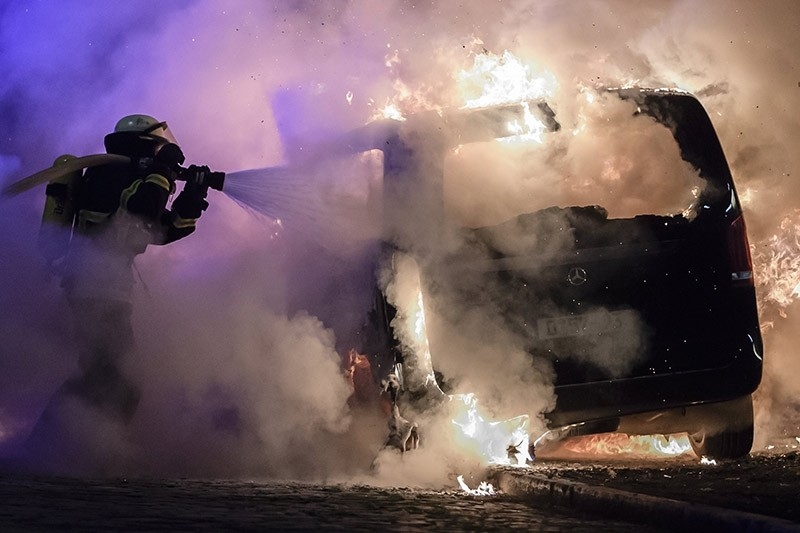 Firefighters extinguish the fire of a burning car during riots at the G20 summit in Hamburg, Germany, 08 July 2017. (EPA Photo)