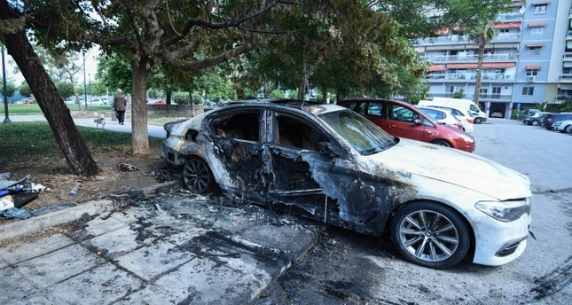 A damaged car belonging to a Turkish national is parked by a block of flats in the northern port city of Thessaloniki, Greece on Monday, June 10, 2019. (AP Photo)