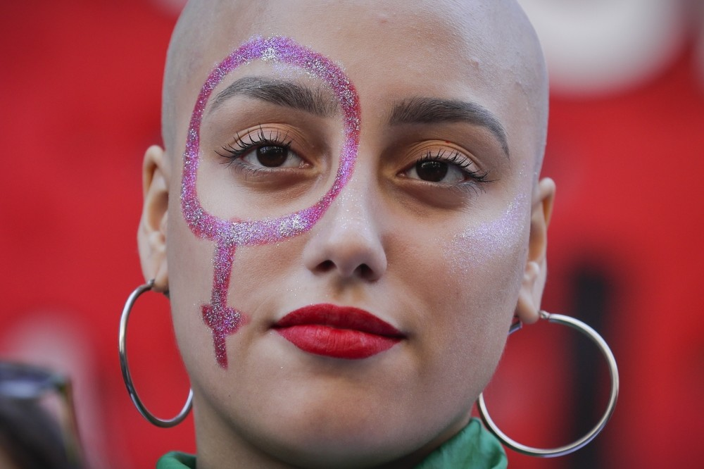 A woman with a Venus symbol painted on her face at a rally in Argentina.