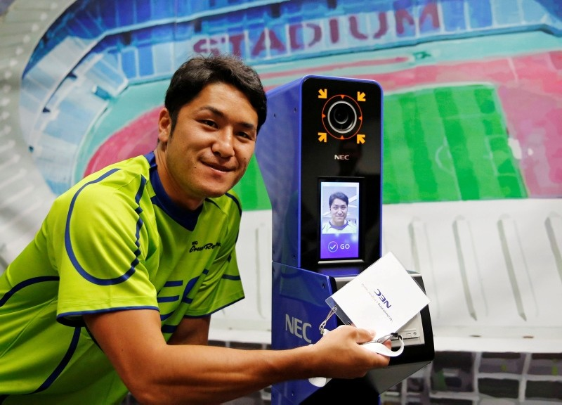 NEC Green Rockets' rugby player Teruya Goto poses with the face recognition system for Tokyo 2020 Olympics and Paralympics, which is developed by NEC corp, during its demonstration in Tokyo, Japan August 7, 2018. (Reuters)