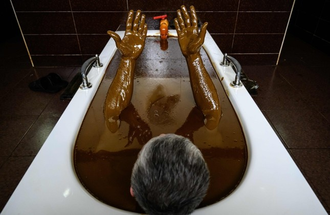A man bathes in a tub filled with Naftalan crude oil during a treatment session at Sehirli Naftalan Health Center, some 300 kilometers (186 miles) from capital Baku, on March 21, 2019. (AFP Photo)