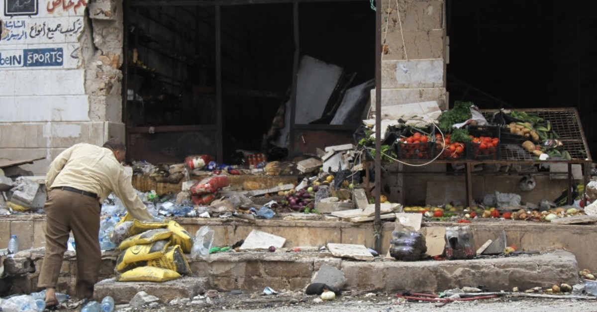 A Syrian man checks debris at a vegetable stall following an airstrike by Syrian regime forces in Maar Shurin on the outskirts of Maaret al-Numan in northwest Syria on July 16, 2019. (AFP Photo)