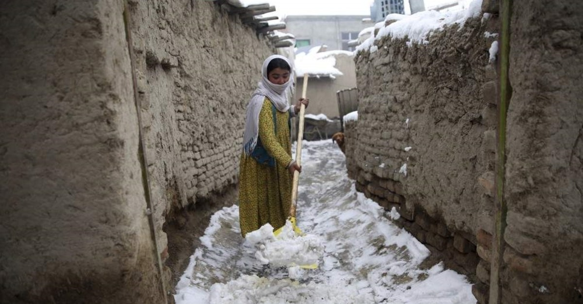 An internally displaced young Afghan woman cleans an alley outside her house on the outskirts of Kabul, Afghanistan, Sunday, Jan. 12, 2020. (AP Photo)
