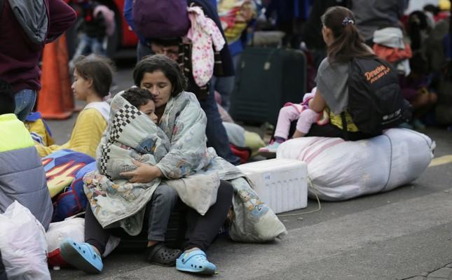 Venezuelan migrants wait outside an immigration processing office on the Rumichaca bridge, Ecuador, June 12, 2019.