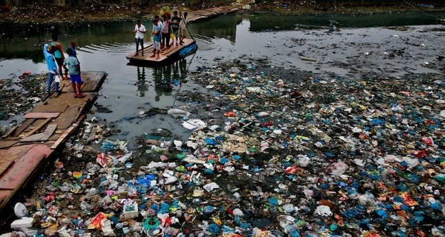 In this Sunday, Oct. 2, 2016 file photo, a man guides a raft through a polluted canal littered with plastic bags and other garbage in Mumbai, India. (AP Photo)