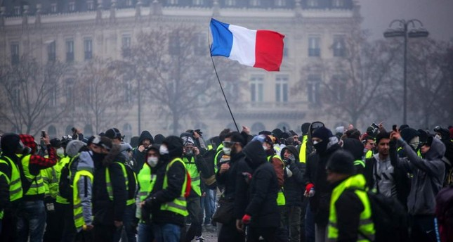 Demonstrators gather near the Arc de Triomphe in central Paris during a protest by the yellow vest movement against rising fuel prices and living costs, Paris, Dec. 1.