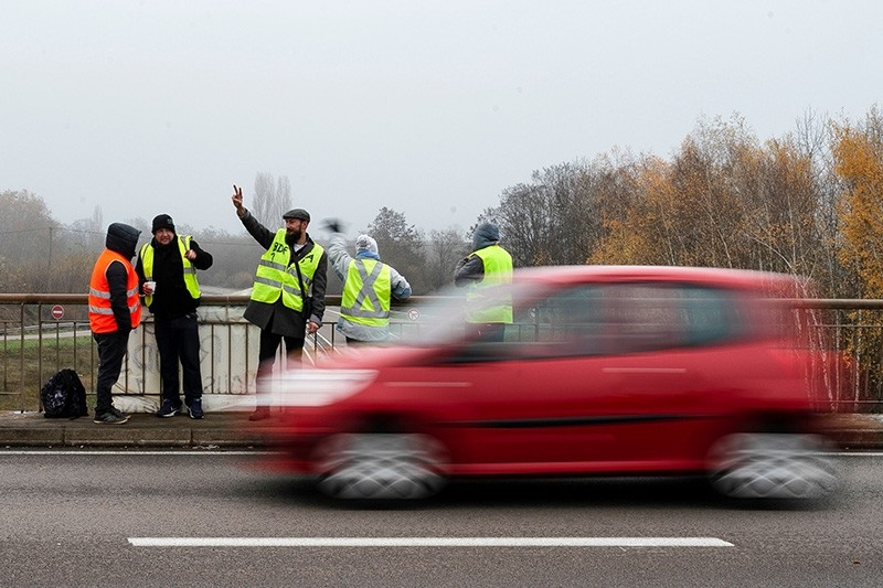 A protestor gestures as a car drives on a bridge over the N70 road on Nov. 23, 2018, near Montceau-les-Mines, central France. (AFP Photo)