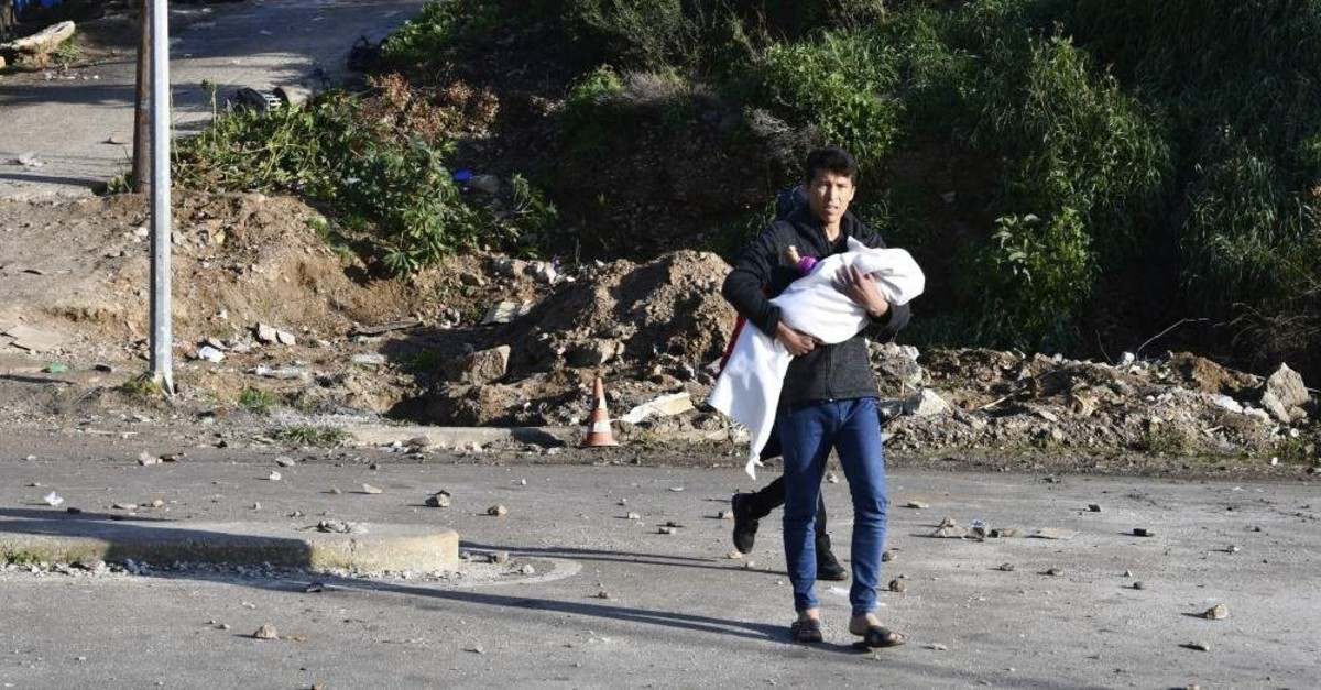A man carries a baby as he walks outside a refugee camp after clashes on the eastern Greek island of Samos, Dec. 19, 2019. (AP Photo)