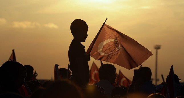 A boy holds a Turkish flag during a rally to honor the victims of the July 15, 2016 failed coup attempt, part of the ceremonies for the three-year anniversary, Istanbul, July 15, 2019.