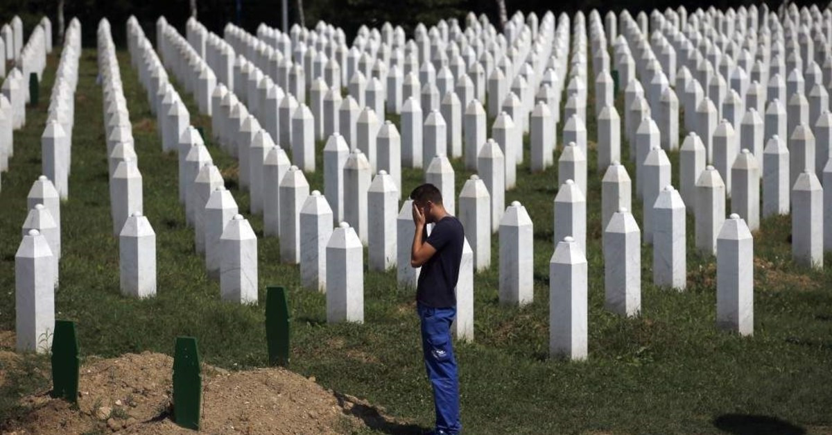 A man prays among gravestones at the memorial center of Potocari, near Srebrenica, Aug. 14, 2018. (AP Photo)