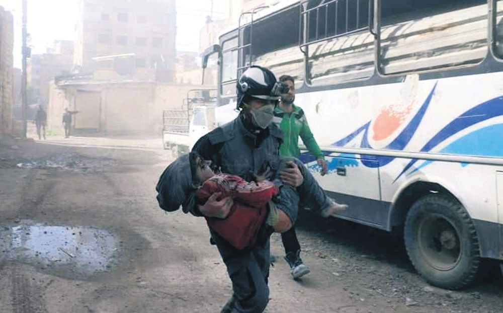 This photo provided by the Syrian Civil Defense White Helmets shows a member of the group carrying a boy wounded in airstrikes and shelling by pro-Assad forces in Eastern Ghouta on Friday.