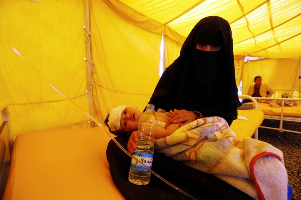 A Yemeni woman holds her cholera-infected child inside a makeshift tent at a hospital in Sanaa, Yemen, July 22.