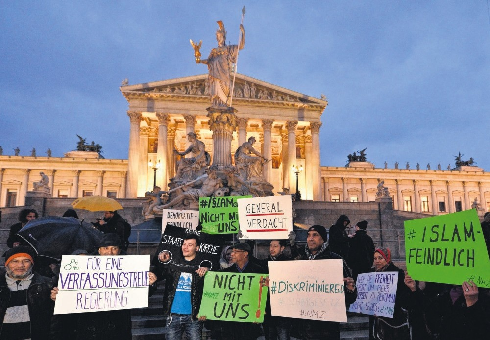 Protesters hold banners during a demonstration organized under the slogan ,New Islam Law? Not with us!, in front of the parliament building in Vienna, Austria, Feb. 24, 2015.