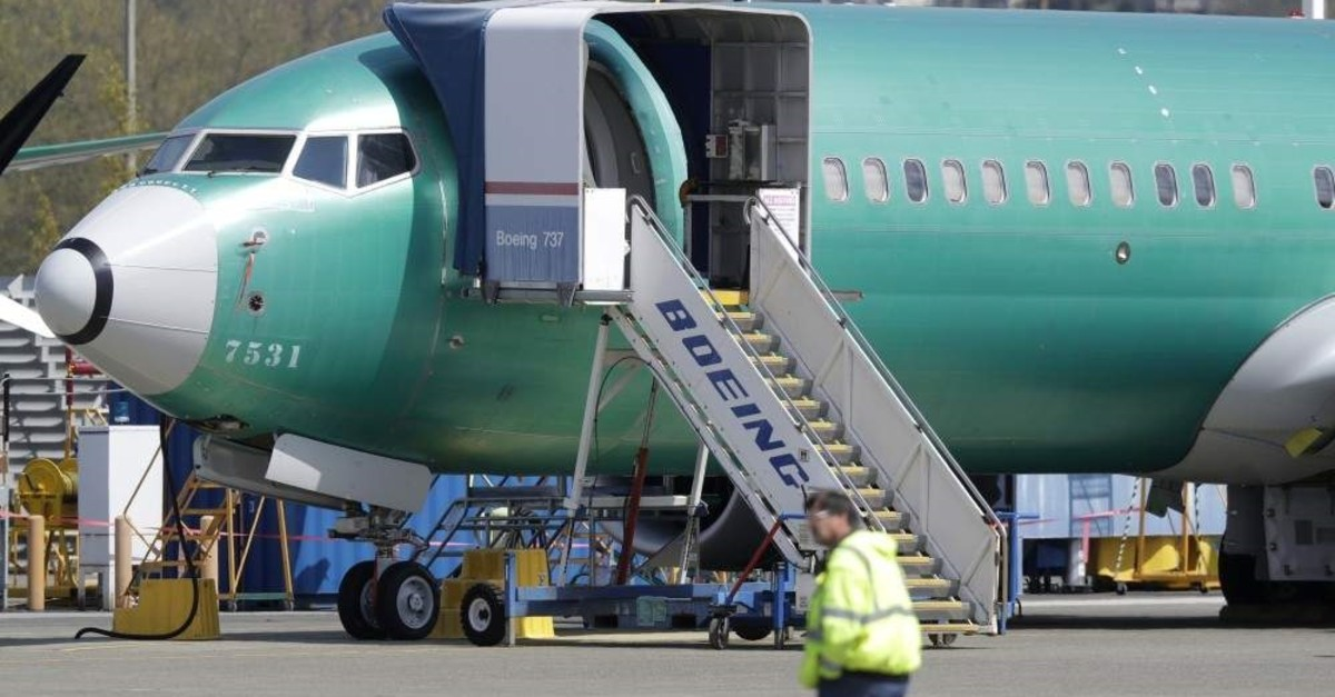 A worker walks past a Boeing 737 Max 8 airplane being at Boeing's assembly facility in Renton, Washington. (AP Photo)