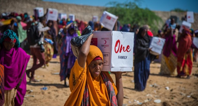 A Somalian woman carries a humanitarian aid delivered by Turkish Red Crescent during drought hit the country earlier this year.