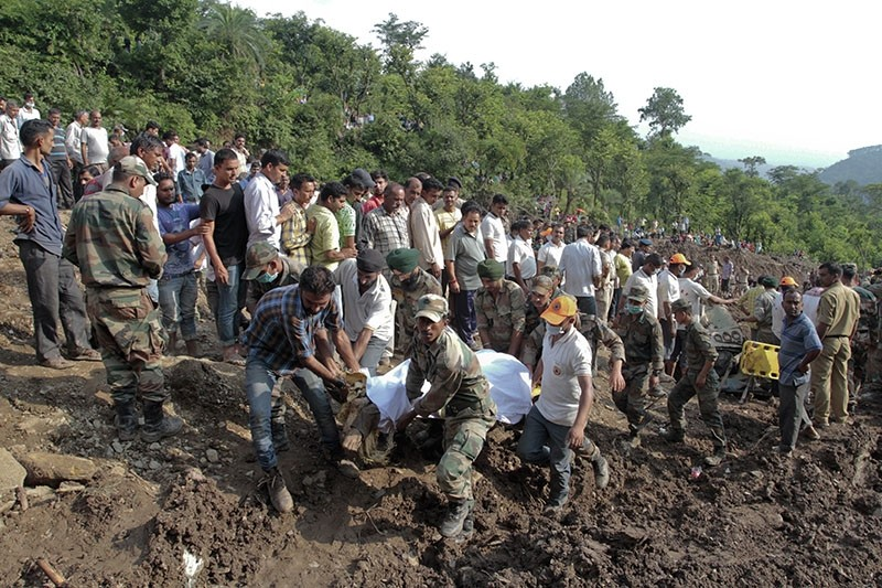 Army soldiers and rescue workers recover bodies of landslide victims even as they try to pull out two buses that were covered in mud after a landslide. (AP Photo)