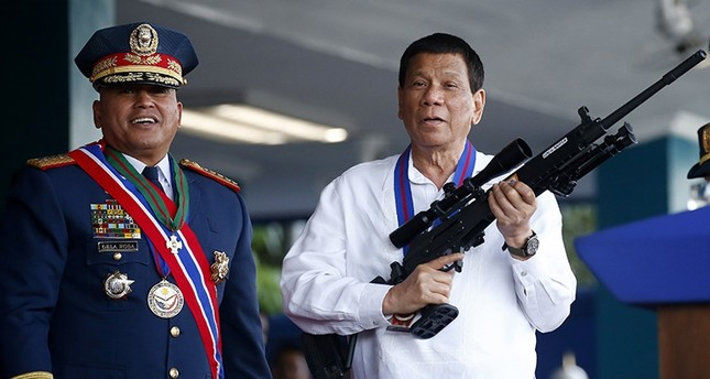 In this April 19, 2018 file photo, Philippine President Rodrigo Duterte jokes to photographers as he holds an Israeli-made Galil rifle. (AP Photo)