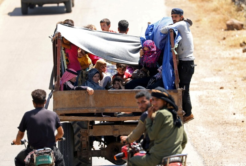 Internally displaced people from Deraa province ride on a back of a truck near the Israeli-occupied Golan Heights in Quneitra, Syria June 30, 2018. (Reuters Photo)