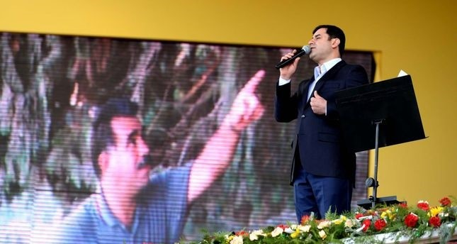 HDP Co-Chair Demirtau015f speaking at a Nevruz gathering in Diyarbaku0131r on Monday with a picture of jailed PKK leader u00d6calan in the background.